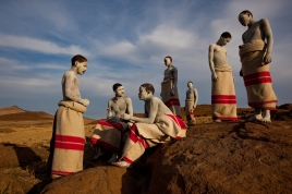 Xhosa teens, in a circumcision ritual, are wrapped in ceremonial blankets and painted with white clay for purification.